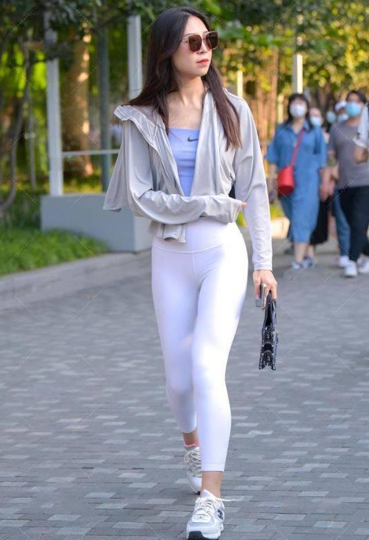 连帽衫宽松外套搭配白色紧身长裤,洒脱飘逸,活力十足