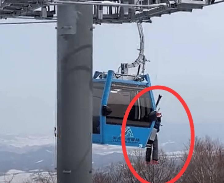 黑龙江一男子侧挂缆车外,身体悬空晃荡,工作者紧急倒回救援