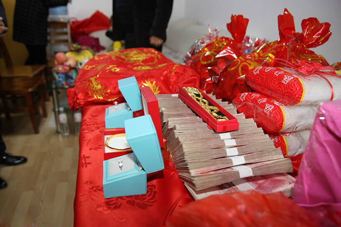 江西情侣订婚,68万现金堆成山,该不该为了面子借钱给彩礼?